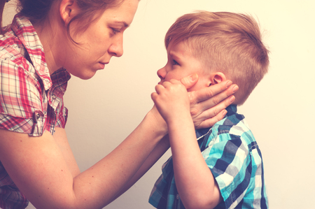 Young mother comforting little crying boy. Sad unhappy child looking to the mom . Family relations problems. Standard-Bild