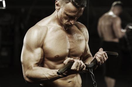 Male bodybuilder working out in machine