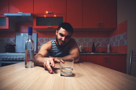 exhausting: Young caucasian man drinking alcohol at home