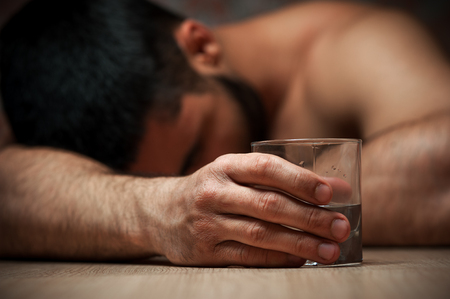 Drunken man sleeping with glass of alcohol