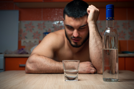 exhausting: Young drunken man sitting in the kitchen at home