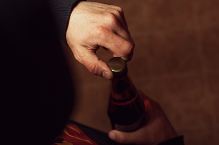 exhausting: Closeup of male hands opening beer bottle.