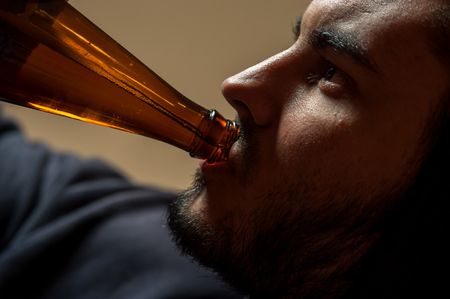 wasted: Young man drinking beer, closeup