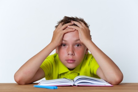 Tween boy sitting at the table with exercise book Stock Photo