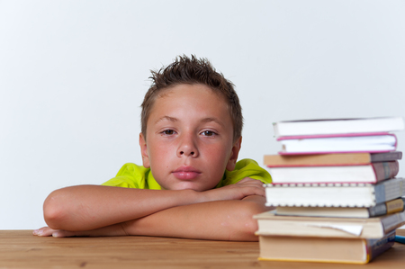 Tween pensive child sitting at table with books