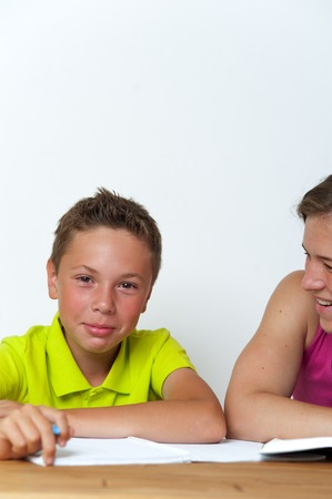 Tween boy doing homework lessons with his mother Stock Photo