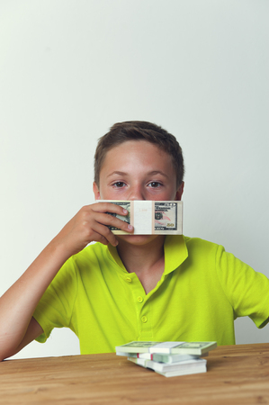 Tween child covering mouth with dollar bills