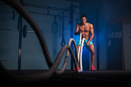 Muscular fitness man working out with battle ropes Фото со стока