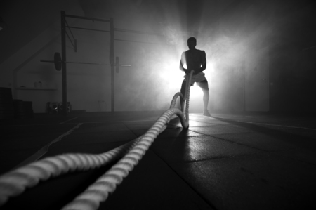 Silhouette of man working out with battle ropes