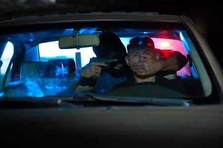 Criminal man pointing a gun at the scared driver