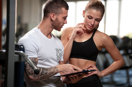 Personal trainer and his female client in gym Stock Photo
