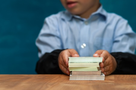 Little stylish boy counting money at workplace Stock Photo