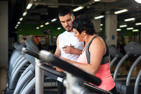 smiing: Smiing middle aged woman and fitness coach in gym