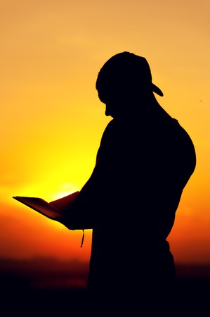 voyage: Silhouette of young man reading a book at sunset Banque d'images