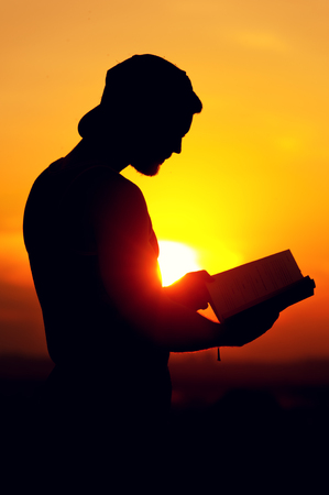 voyage: Silhoette of relaxed man reading a book at sunset