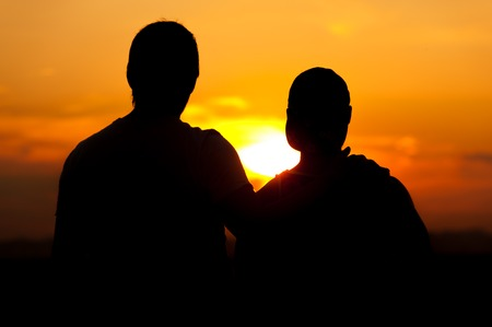 voyage: Two men enjoying sunset time together Banque d'images