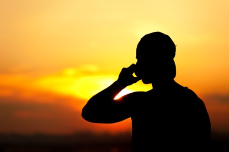 voyage: Silhouette of young man talking on the phone