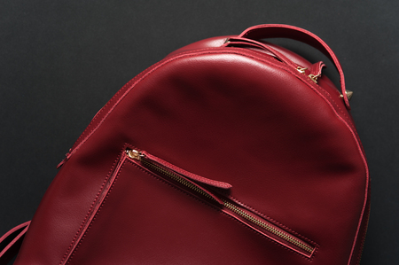 clutch bag: Red leather backpack on grey background