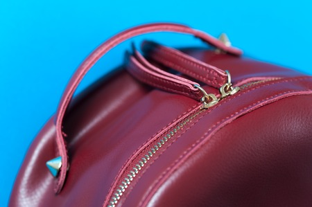 Red leather backpack on blue background