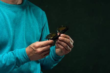 Closeup man holding stylish eyeglasses in hands