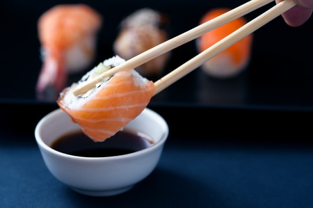 Chopstick with sushi roll and soy sauce, closeup Stock Photo
