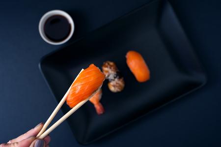 Sashimi sushi set on black plate, closeup.