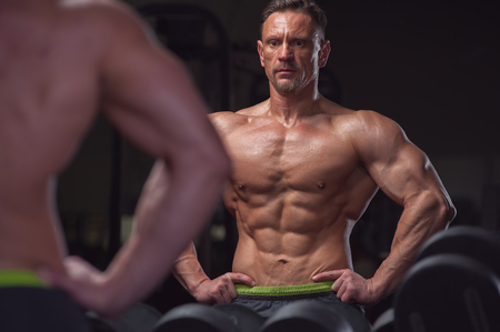 Handsome bodybuilder posing in gym