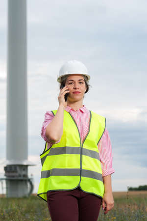 Portrait of a beautiful positive woman engineer in a green vest shirt with talking on smartphone against the backdrop of a windmill