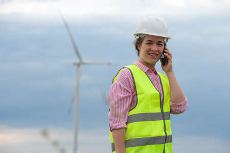 Female chief architect in a green waistcoat holds an smartphone against a background of blurry windmills