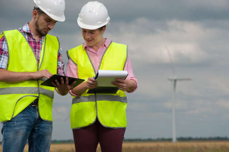 Concept of alternative energy and windmills. Two engineers in white helmets and green vests with working plans on the background of windmills farm Imagens