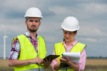 Two Successful ambitious young architects in a green vest and white hard hat designing a plan against a background of windmills Imagens