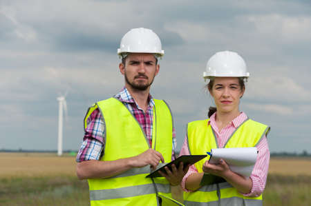 Concept of alternative energy and windmills. Two engineers in white helmets and green vests with working plans on the background of windmills farm 版權商用圖片