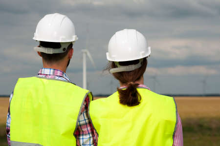 Concept of alternative energy and windmills. Rear view of two engineers in white helmets and green vests looking somewhere into the distance