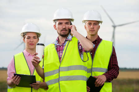 Concept of alternative energy and windmills. Team work - Three engineers in white helmets and green vests on the background of windmills farm