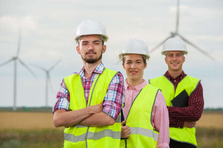 Group of young ambitious engineers or architects in white helmets and green vests standing against windmills and sky