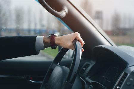 Close-up - businessman driving luxury car. Stock Photo