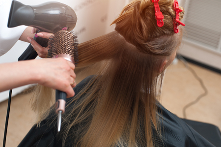Hairstyler with a brush drying hair of a woman in a salon