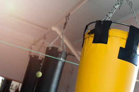 Punching bag hanging on chains on the ceiling Stock Photo