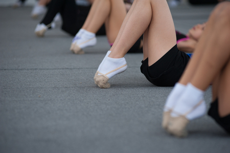 Close up of feet of girls stretching tip toes in gym