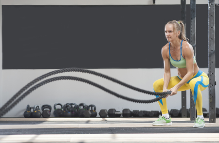Side view - sporty woman training with battle ropes