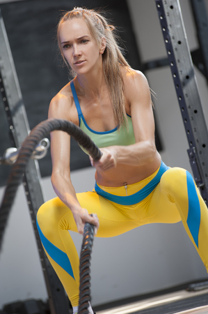 Battle ropes workout. Portrait of Sporty Athletic Girl During high intensive cardio or cross power training.