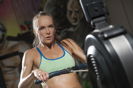 Sporty Blonde woman exercising on rowing machine