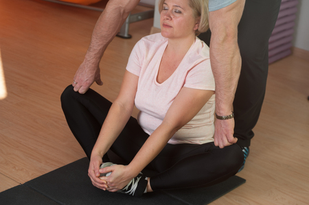 Middle aged woman does stretching after a workou