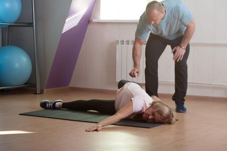An aged woman does stretching after a workou Фото со стока