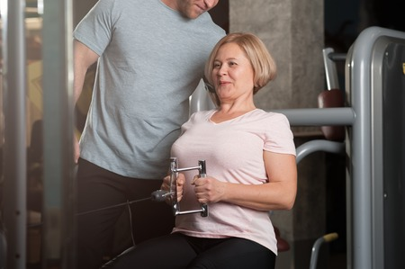 A male trainer helps his female client