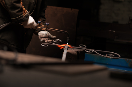 Blacksmiths Hand In Protective Gloves Solder A Metal Stock Photo
