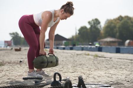 Athletic woman training with sand bag at the seaside
