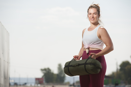 Young fit woman training with sand bag on the beach