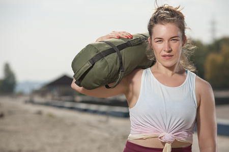 Portrait of attractive smiling woman training at the beach Imagens