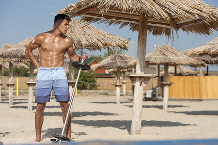 Athletic young handsome with naked body on the beach